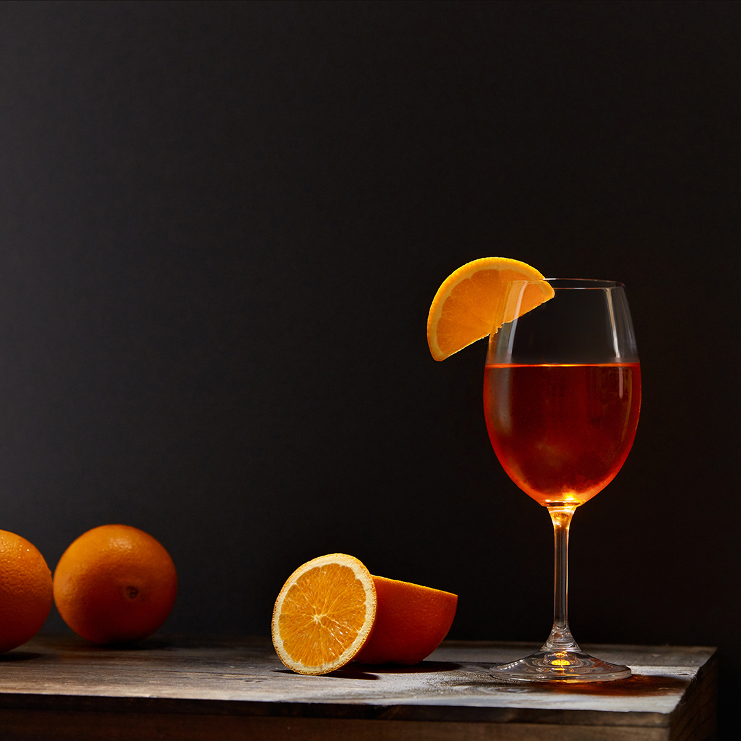 Oranges and drink on wooden table photographed by professional food and beverage photographer Kate Benson.