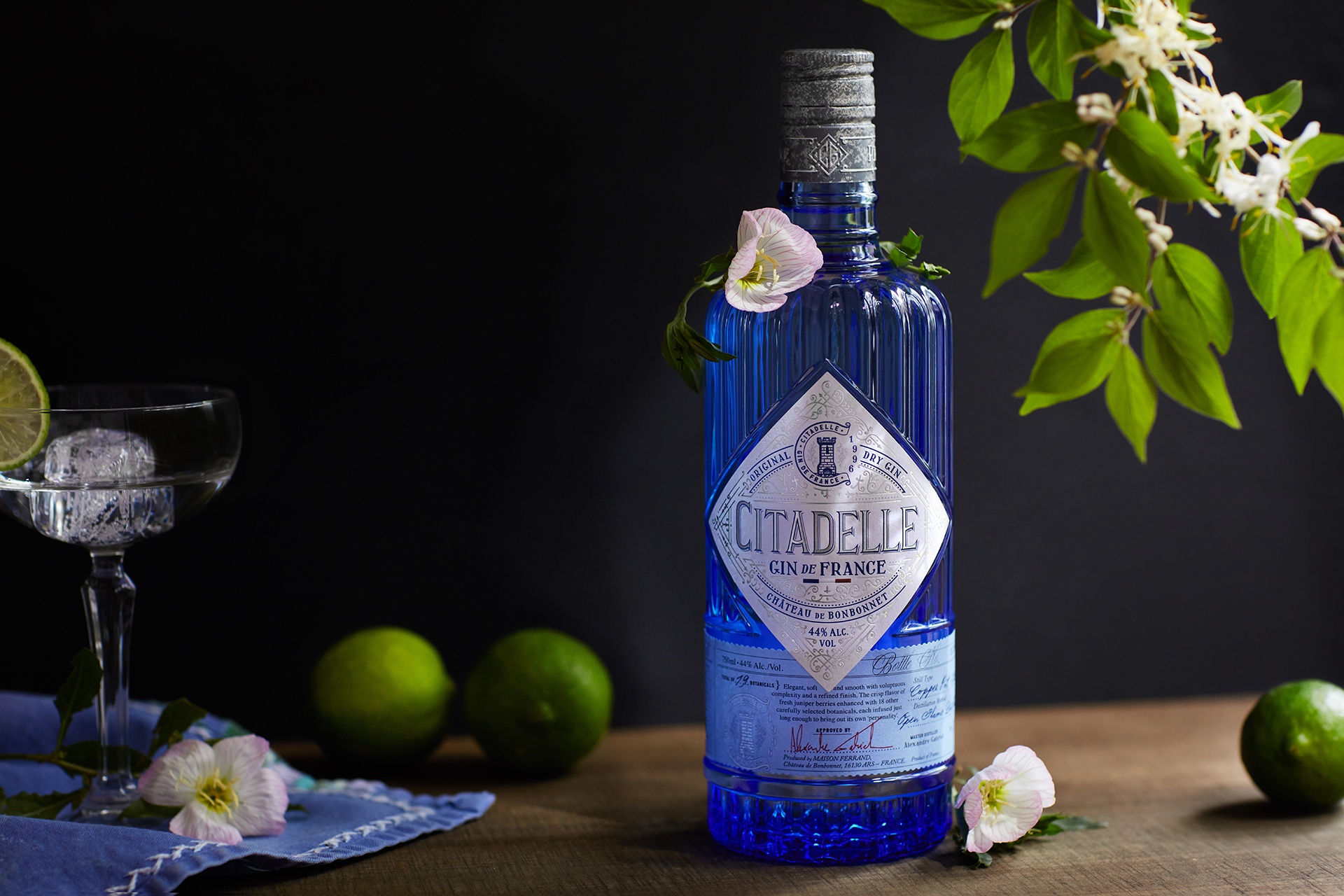 Gin bottle with glass, limes, and flowers, styled and photographed by Kate Benson, professional food and beverage photographer.