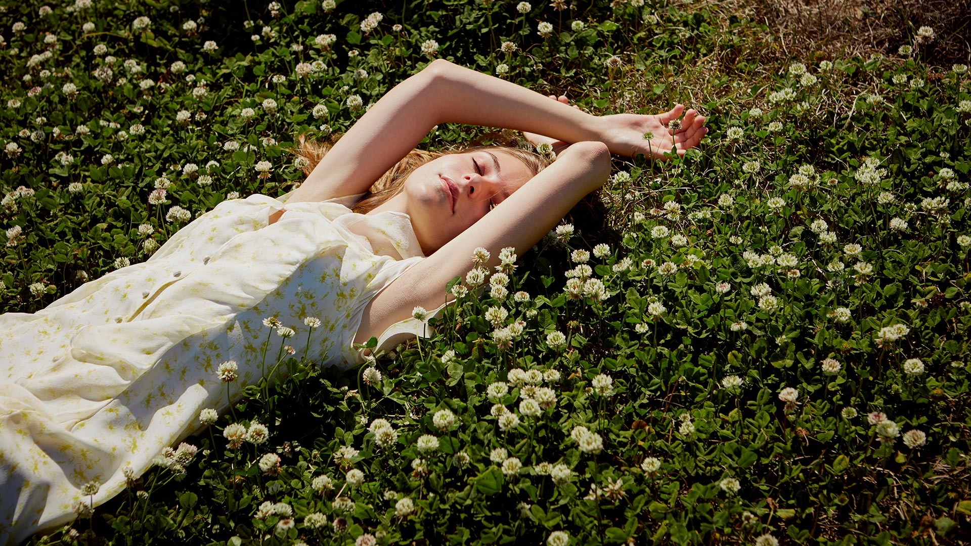 Model laying in field of clover flowers photographed by fashion apparel photographer Kate Benson
